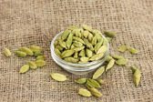 Cardamomo verde in ciotola di vetro su tela close-up sfondo — Foto Stock