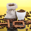 Composition of canvas sack and the cup with coffee beans on bright background. Hot. — Stock Photo