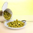 Open tin can and plate with peas and spoon on wooden table on green background — Stock Photo #11961658