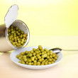 Open tin can and plate with peas and spoon on wooden table on green background — Stock Photo