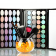 Make-up brushes in a bowl with stones on palette of shadows background - Stock fotografie