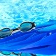 Blue flippers and goggles on blue sea background - Stock Photo