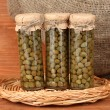 Glass jar with tinned capers on wooden background close-up — Stock Photo #11962334