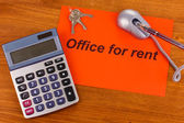 Advertise rental office on red paper on wooden background — Stock Photo
