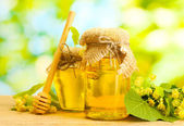 банки с линден мед и цветы на деревянный стол на зеленом фоне — Стоковое фото