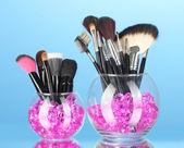 Make-up pinsel in zwei schalen mit steinen auf blauem hintergrund — Stockfoto