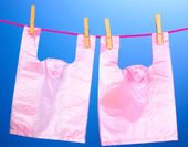 Cellophane bags hanging on rope on blue background — Stock Photo