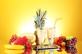 Milk shakes with fruit on yellow background close-up — Stock Photo