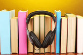 Headphones on books on wooden table on yellow background — Stock Photo