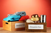 Donation boxes with clothing and food on red background close-up — Stock Photo