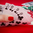 Woman's hand holding playing cards straight flush - Stok fotoğraf