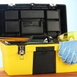 Open yellow tool box with tools on blue background close-up — Stock Photo #11999117