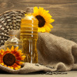 Oil in bottles, sunflowers and seeds, on wooden background — Stock Photo #11999408