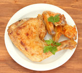 Roasted chicken wings and leg with parsley in the plate on wooden background close-up — Stock Photo