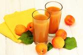 очки абрикосовый сок и свежие абрикосы на белый деревянный стол — Стоковое фото