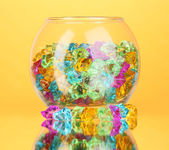 A glass with colorful decorative stones on yellow background close-up — Stock Photo
