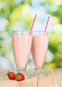 Strawberry milk shakes on wooden table on bright background — Stock Photo