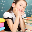 Little schoolgirl and books in classroom near blackboard - Stock Photo