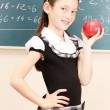 Beautiful little girl in school uniform with apple in class room — Stock Photo