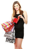 Beautiful young woman with shopping bags and credit card isolated on white — Stock Photo