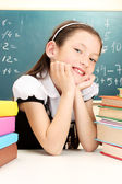 Little schoolgirl and books in classroom near blackboard — Stock Photo