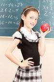 Beautiful little girl in school uniform with apple in class room — Stock Photo