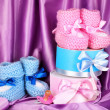 Pink and blue baby boots, pacifier and gifts on silk background — Stock Photo #12042464