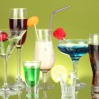 Variety of alcoholic drinks on green background — Stock Photo #12042707