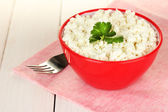 Cottage cheese with parsley in red bowl and fork on pink napkin on white wooden table close-up — Stock Photo