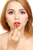 Beautiful woman is applying her lips with red lipstick — Stock Photo