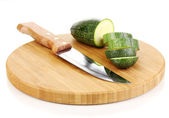 Sliced zucchini on chopping board isolated on white — Stock Photo
