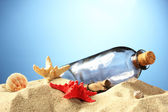 Glass bottle with note inside on sand, on blue background — Stock Photo