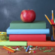 Composition of books, stationery and an apple on the teacher's desk in the background of the blackboard — Stock Photo #12065578
