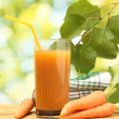 Royalty-Free Stock Photo: Glass of carrot juice and fresh carrots on wooden table on green background