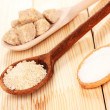 White and brown sugar in spoons on wooden background — Stock Photo