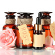 Bottles of oil and roses isolated on white — 图库照片