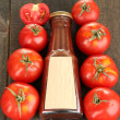 Ketchup in bottle and tomatoes on wooden table — Stock Photo #12066761