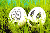 White eggs with funny faces in green grass — Stock Photo