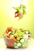 Fresh vegetable salad in transparent bowl with spoon and fork on green background — Stock Photo