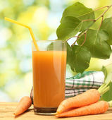 Glass of carrot juice and fresh carrots on wooden table on green background — Stock Photo