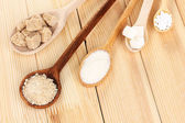Sweetener with white and brown sugar in spoons on wooden background — Stock Photo