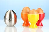 Zegar jaj oraz jaj w kolorze stoją na niebieskim tle — Zdjęcie stockowe