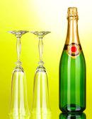 Bottiglia di champagne e calici su sfondo verde — Foto Stock