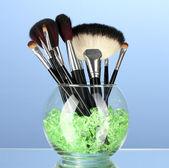 Make-up pinsel in eine schüssel geben, mit steinen auf blauem hintergrund — Stockfoto