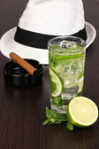Mojito and a hat on a wooden background — Stock Photo