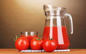 Tomato juice in pitcher and glass on wooden table on brown background — Stock Photo