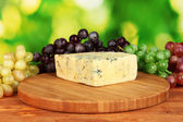 Cheese with mold on the cutting board with grapes on bright green background — Stock Photo