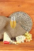 Composizione del formaggio blu e un bicchiere di vino con uve sul primo piano sfondo in legno — Foto Stock