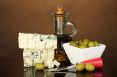 Cheese with mold and olives on brown background close-up — Stock Photo