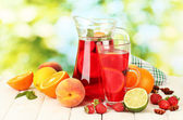 Sangria in jar and glass with fruits, on wooden table, on green background — Stock Photo